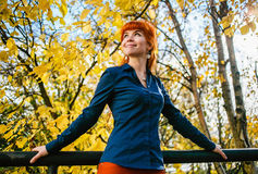 Beautiful woman in autumn park with yellow leaves background. Concept of heat, positive energy, nature enjoy. Stock Image