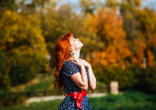 Beautiful woman in autumn park with yellow leaves background. Concept of heat, positive energy, nature enjoy. Royalty Free Stock Image