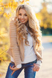 Beautiful woman in autumn park. Beautiful young woman with long blonde curly hair,autumn jacket beige,posing for the photographer on the background of shrubs stock photography