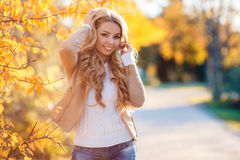 Beautiful woman in autumn park. Beautiful young woman with long blonde curly hair,autumn jacket beige,posing for the photographer on the background of shrubs stock image