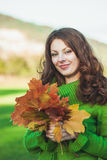 Beautiful woman with  autumnal maple leaves Stock Photos