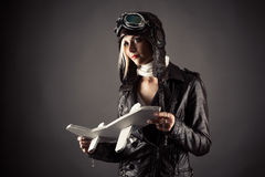 Beautiful woman in aviator hat standing with toy airplane in hand Royalty Free Stock Photo