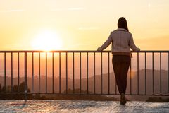 Beautiful woman back shot on a viewpoint railing during sunset with blurred background stock photos