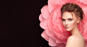 Beautiful woman on the background of a large flower. Beauty summer model girl with pink peony. Young woman with elegant hairstyle and makeup. Fashion photo stock photo