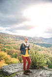 Beautiful woman with backpack against colorful sunny autumn fore. Beautiful woman with backpack, holding binoculars, standing on a rock against colorful autumn Stock Images