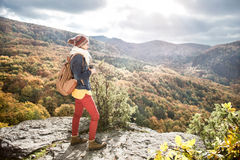 Beautiful woman with backpack against colorful sunny autumn fore. Beautiful woman with backpack, holding binoculars, standing on a rock against colorful autumn Royalty Free Stock Photo
