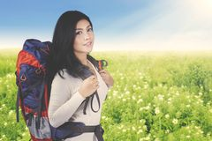 Beautiful woman with backpack in the flower field royalty free stock photos
