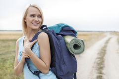 Beautiful woman with backpack looking away while hiking at field Royalty Free Stock Image