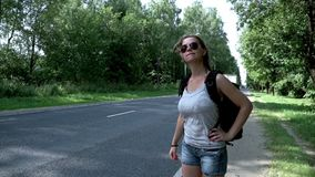 Beautiful woman with backpack and sunglasses hitch hiking car on road. Young woman traveler with backpack hitchhiking on road on summer day. Hitchhiking woman stock video footage