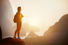Beautiful woman with backpack at sunrise or sunset on mountain top Stock Photo