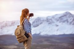 Woman with backpack taking photo of mountain stock photo