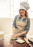 Beautiful woman baking. Beautiful young woman in apron and chef hat is looking at camera and smiling while kneading the dough in the kitchen Stock Photography