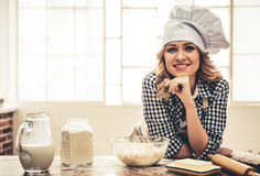 Beautiful woman baking. Beautiful young woman in apron and chef hat is looking at camera and smiling while kneading the dough in the kitchen Royalty Free Stock Photo