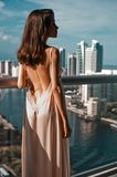 Beautiful woman on balcony. Young beautiful woman on balcony overlooking the cityscape with skyscrapers. Beautiful morning. Fashion and beauty stock photography