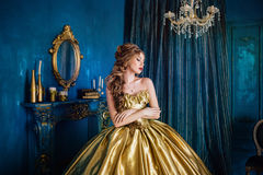 Beautiful woman in a ball gown. Beautiful woman in a golden ball gown in the great blue interior Stock Image