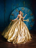 Beautiful woman in a ball gown. Beautiful woman in a golden ball gown in the great blue interior Stock Photography