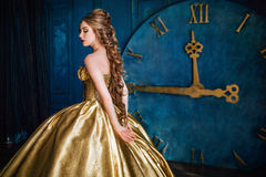 Beautiful woman in a ball gown. Beautiful woman in a golden ball gown in the great blue interior Royalty Free Stock Photos