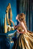 Beautiful woman in a ball gown. Beautiful woman in a golden ball gown in the great blue interior Stock Photo