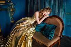 Beautiful woman in a ball gown. Beautiful woman in a golden ball gown in the great blue interior Stock Images