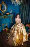 Beautiful woman in a ball gown. Beautiful woman in a golden ball gown in the great blue interior Stock Photos