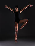 Beautiful woman ballerina in black body suit jumping over black Stock Photos