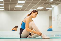 Beautiful woman ballerina doing warm up in the gym royalty free stock images