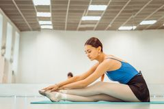 Beautiful woman ballerina doing warm up in the gym stock image