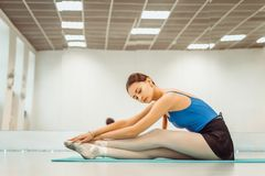 Beautiful woman ballerina doing warm up in the gym stock images