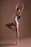 Beautiful woman ballet dancer over beige Royalty Free Stock Photos