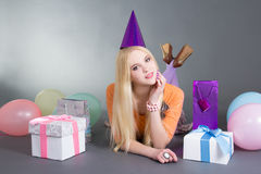 Beautiful woman with balloons lying over grey Royalty Free Stock Photo