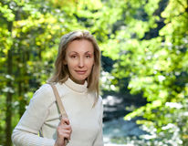 The beautiful woman on the bank of the lake against bright green foliage.Portrait in a sunny day Royalty Free Stock Photo