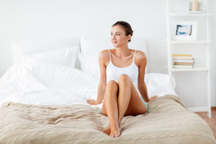 Beautiful woman with bare legs on bed at home Royalty Free Stock Photos