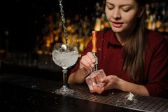 Beautiful woman barman preparing an ice cube for making an Apero Stock Images