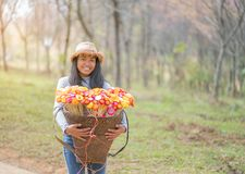 Beautiful woman with  basket of colorful flower. Walking in the forest Royalty Free Stock Image
