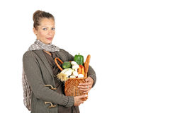 Beautiful woman with a basket full of vegetables Stock Photography