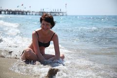 A beautiful woman is basking in the sun in the sea. Stock Image