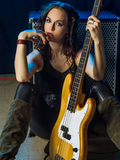 Beautiful woman bass player. Photo of a beautiful woman bass player sitting in front of her amplifier Royalty Free Stock Images