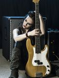 Beautiful woman bass player sitting with her amp. Photo of a beautiful woman bass player sitting in front of her amplifier Stock Image