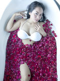 Beautiful woman in bath with rose petals Royalty Free Stock Photos
