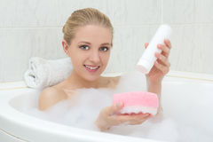 Beautiful woman in bath with sponge and shower gel Royalty Free Stock Photography