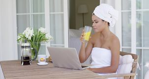 Beautiful woman in bath towel using laptop stock video footage