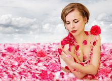 Milk river with rose petals. Beautiful woman bathes in a milk river with rose petals royalty free stock photo