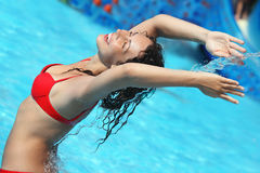 Beautiful woman bathes in pool under water stream. Smiling beautiful woman bathes in pool under water stream, lifted hands upwards Royalty Free Stock Photos