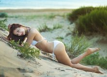 Beautiful woman in a bathing suit lying on the sand. By the sea shore Royalty Free Stock Photo