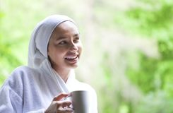 Beautiful woman in bathrobe drinking coffee. Young woman enjoying her coffee. She is wearing white cozy bathrobe and standing near the window royalty free stock photos