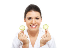 Beautiful woman in bathrobe holding cucumbers. Stock Photo