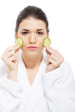 Beautiful woman in bathrobe holding slices of cucumber. Royalty Free Stock Photo