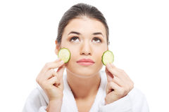 Beautiful woman in bathrobe holding slices of cucumber. Stock Photo