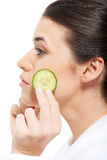 Beautiful woman in bathrobe holding slices of cucumber. Royalty Free Stock Photos