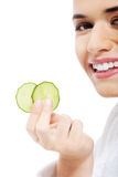Beautiful woman in bathrobe holding slices of cucumber. Stock Images